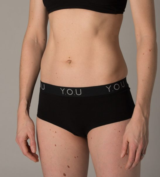 Woman Wearing The Women Branded Boy Shorts in Black, Side View by YOU Underwear at Nurture Collective