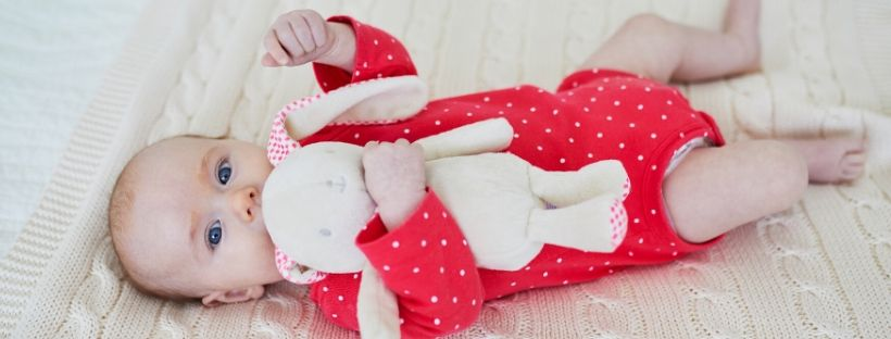 A baby wearing a red babygrow holding a baby comforter for nurture collective blog.