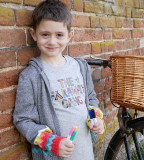 Boy wearing a t shirt and knitted cardigan holding colouring pens Creative Tee Faraway Gang at Nurture Collective