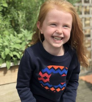 Girl smiling wearing Narrator Sweatshirt Navy by the Faraway Gang at Nurture Collective