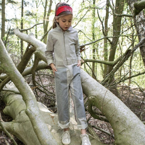 Girl standing in the woods wearing Jackalo Mac Coveralls at Nurture Collective