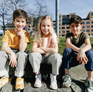 three kids sitting down and smiling on sunny day in the city wearing Jackalo pants at Nurture Collective