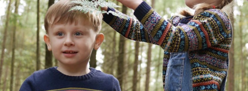 Two Children playing in the woods wearing the Faraway Gang jumpers at Nurture Collective
