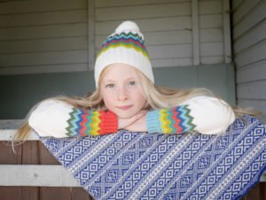Girl leaning on stables doors wearing the Wayfinder merino wool Hat by the Faraway Gang at Nurture Collective