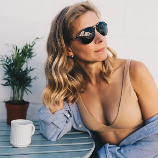 Woman Wearing the Nude Bralette non Wired sitting with sunglasses on by YOU Underwear at Nurture Collective