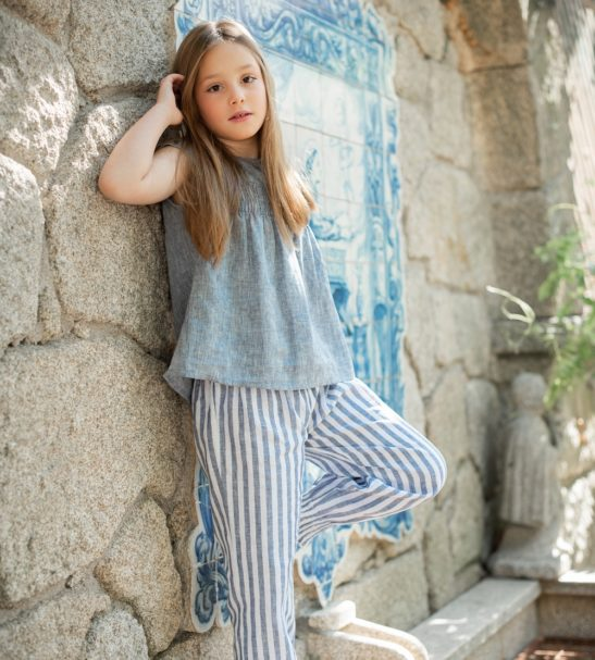 A girl leaning against a wall wearing Jasmine Stripes Pants by Peter Jo at Nurture Collective