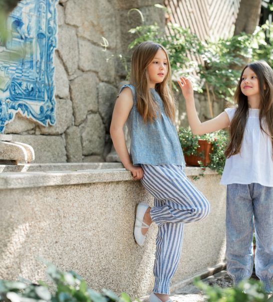 Two girls leaning against a wall wearing Jasmine Stripes Pants by Peter Jo at Nurture Collective