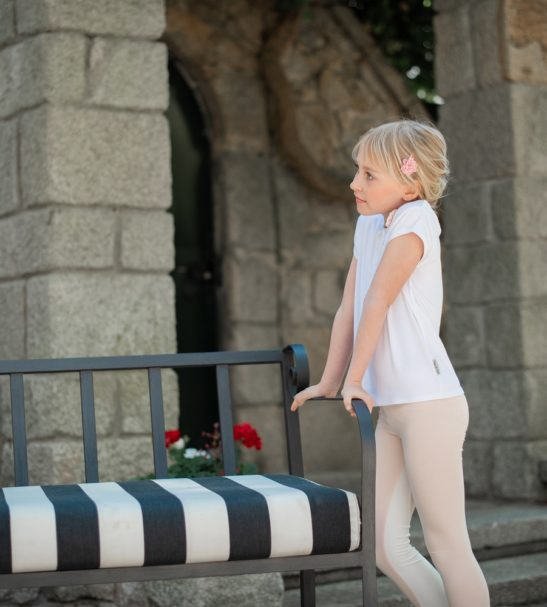 A girl standing leaning on a bench wearing Inversion leggings by Peter Jo at Nurture Collective