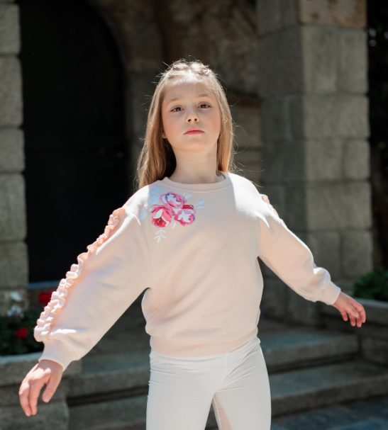 A girl wearing Fairy Pink Sweatshirt and Inversion leggings by Peter Jo at Nurture Collective