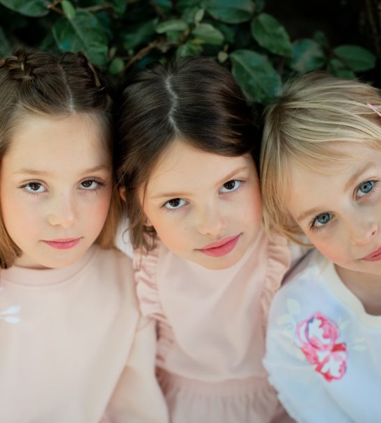 Three girls looking round a corner wearing Fairy Pink Sweatshirt and Inversion leggings by Peter Jo at Nurture Collective