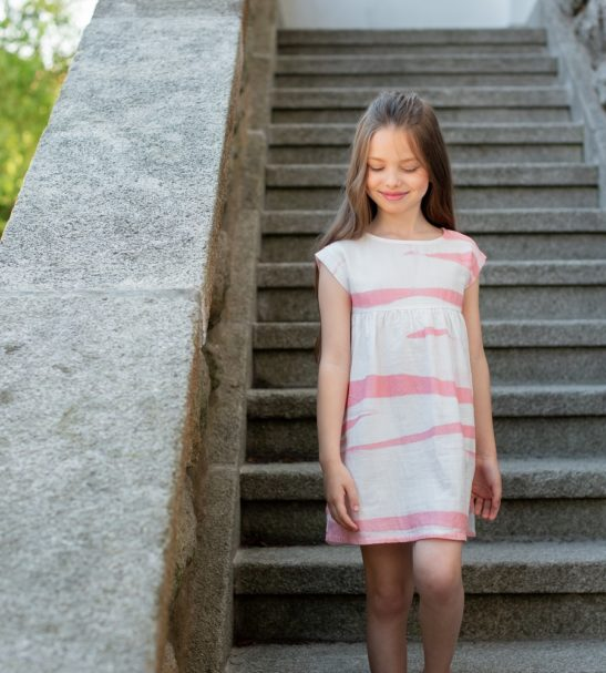 A girl standing wearing Felicity Peach Dress by Peter Jo at Nurture Collective