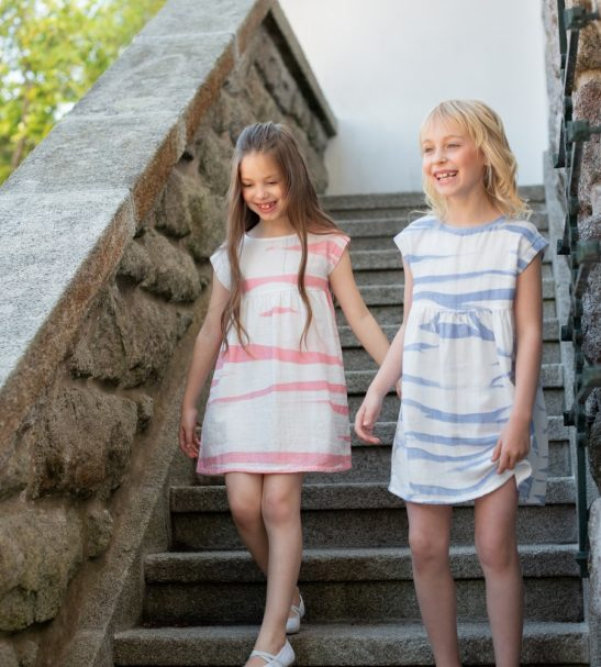 Two girls walking down stairs wearing Felicity Peach and Blue Dress by Peter Jo at Nurture Collective