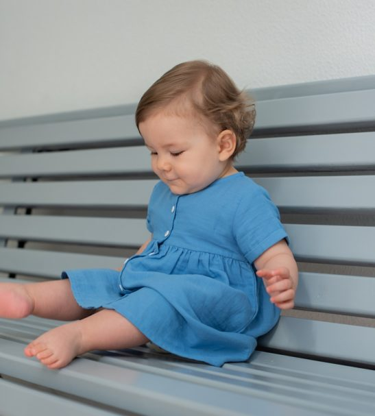 Baby sitting the bench wearing the Harmony Blue Lagoon Cotton Summer Dress in Blue by Peter Jo at Nurture Collective