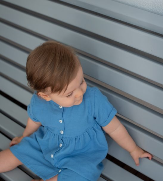 Baby sitting the bench close up view wearing the Harmony Blue Lagoon Cotton Summer Dress in Blue by Peter Jo at Nurture Collective