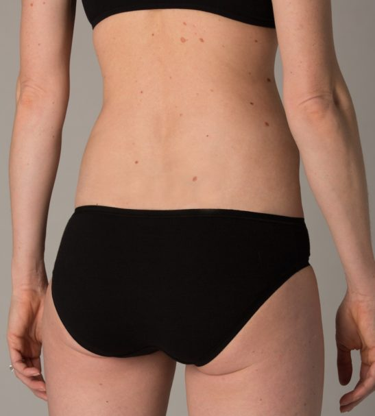 Back view of the model the black set of bikini underwear organic by You Underwear at Nurture Collective
