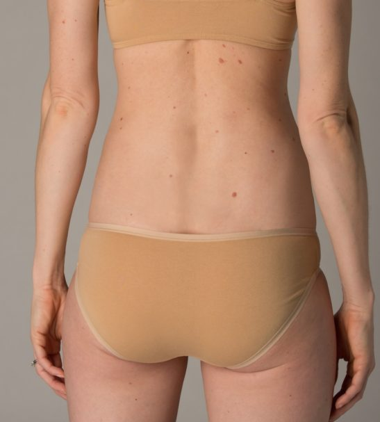 Back view of Model wearing organic nude bralette and bikini pants by You Underwear at Nurture Collective