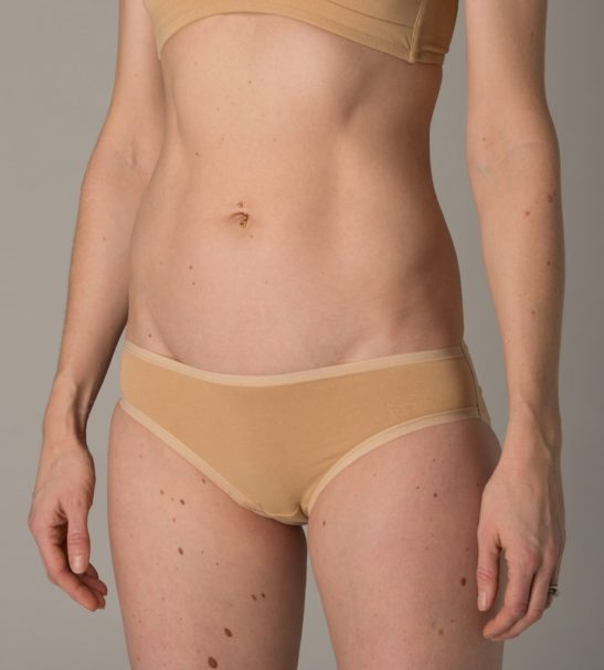 Side view of Model wearing organic nude bralette and bikini pants by You Underwear at Nurture Collective