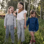 Three girls standing in the forest wearing Jackalo clothing at Nurture Collective