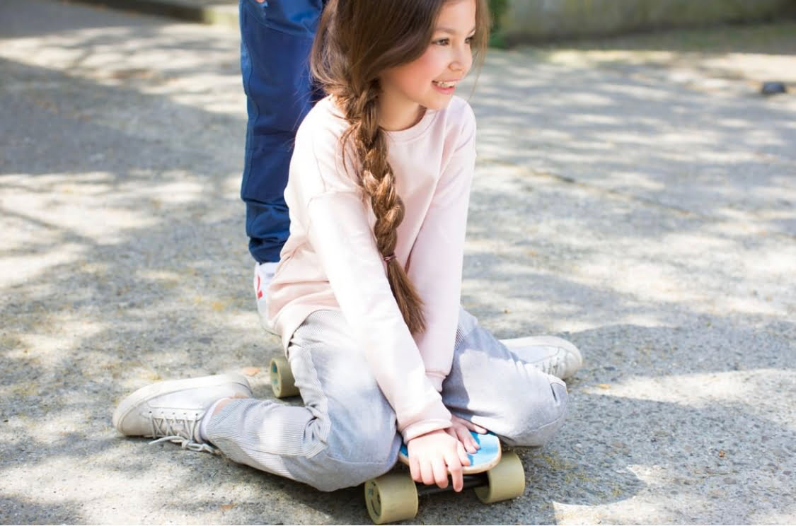 A Girl sitting on a skateboard wearing Engineer Stripe Pants by Jackalo at Nurture Collective