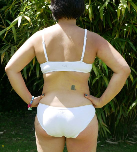 Model standing with her hands hips wearing the white set of underwear organic by You Underwear at Nurture Collective