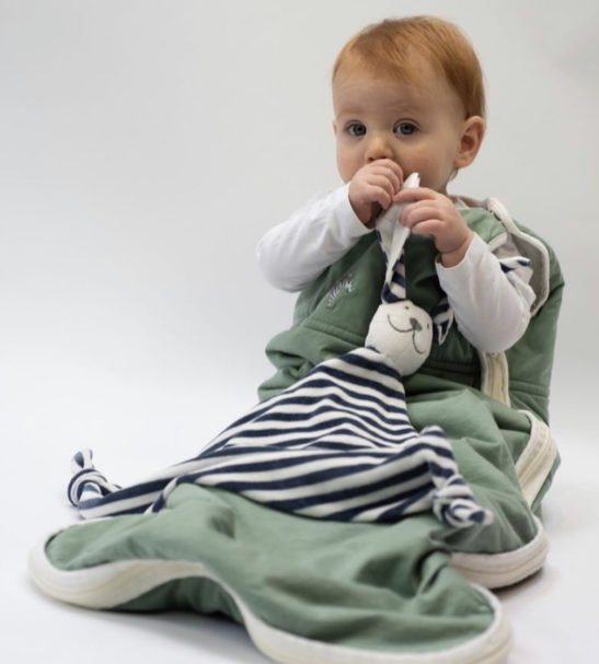 One babysucking his thumb holding the Bunny Comforter in a Sleeping Bag by Little Earth Baby at Nurture Collective
