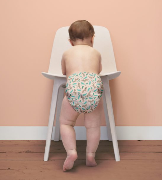 A Baby standing facing and leaning on a chair wearing Wild Cat Print Cloth Nappy by Bambinomio at Nurture Collective