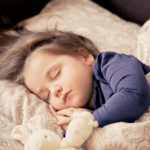 Child sleeping in bed for Nurture Collective Blog tips for better bedtimes