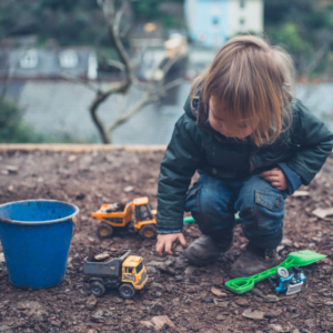 A child playing outside in the mud with trucks for Nurture Collective Blog tips for The better bedtime Blog