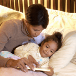 Mum reading daughter a bedtime story in bed before Nurture Collective Blog tips for The better bedtime Blog