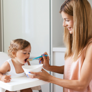mum feeding her baby weaning food in a highchair for Nurture Collective blog