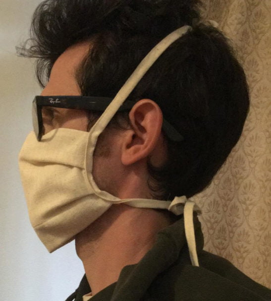 Man wearing the organic cotton face mask WDICF one size at Nurture Collective