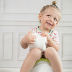 Girl sitting on a potty with toilet paper for 5 tips for stress free potty training
