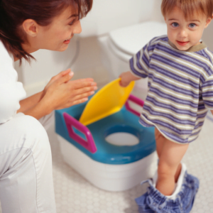 a boy standing next to his potty with his mum for 5 tips for stress free potty training