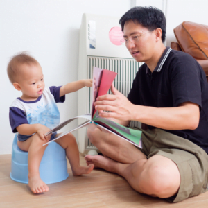 a father reading to his son whilst sitting on the potty for 5 tips for stressful free potty training