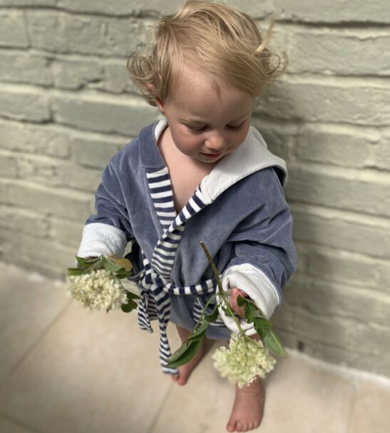 Baby standing in the Grey Velor dressing gown robe holding flowers by Little Earth Baby at Nurture Collective