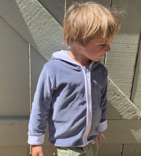 one boy standing on the grass wearing grey velour jacket by Little Earth Baby at Nurture Collective