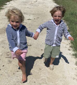two kids happy as can be holding hands and running down in the sand wearing striped velour jacket by Little Earth Baby at Nurture Collective