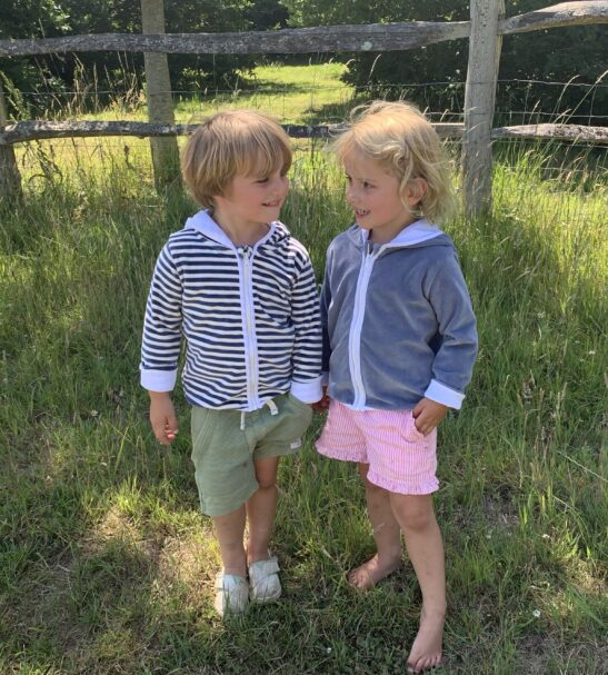 two kids happy as can be holding hands standing on the grass wearing striped velour jacket by Little Earth Baby at Nurture Collective