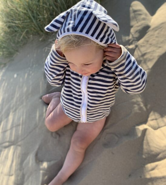 Baby sitting in the sand wearing the Organic Velour Stripy Jacket by Little Earth Baby at Nurture Collective