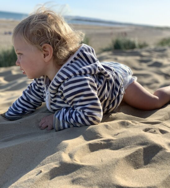 Baby on his tummy in the sand wearing Organic Velour Stripy Jacket by Little Earth Baby at Nurture Collective