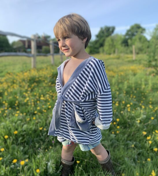 Boy standing in grass wearing the striped Velour dressing gown robe by Little Earth Baby at Nurture Collective