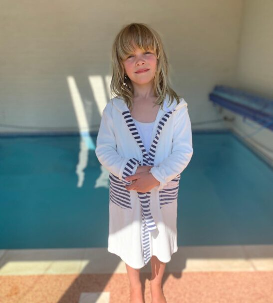 Girl stand by a swimming pool wearing the White Stripy Velour dressing gown robe by Little Earth Baby at Nurture Collective