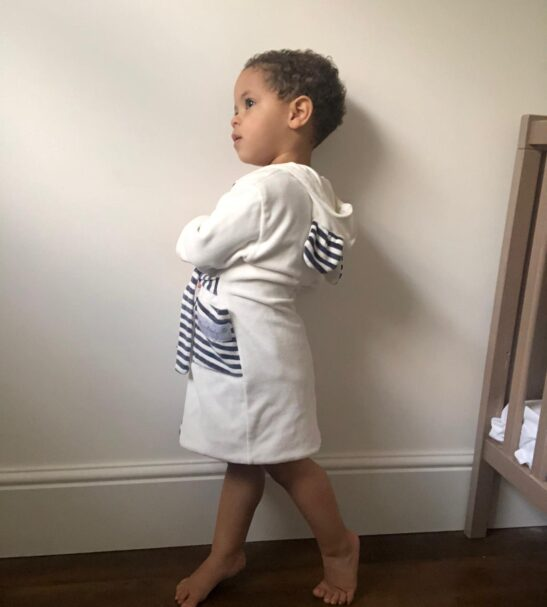 Baby standing leaning against the wall wearing White Striped dressing gown Velour robe by Little Earth Baby at Nurture Collective