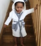 Walking down the stairs wearing the White Stripy Velour robe by Little Earth Baby at Nurture Collective