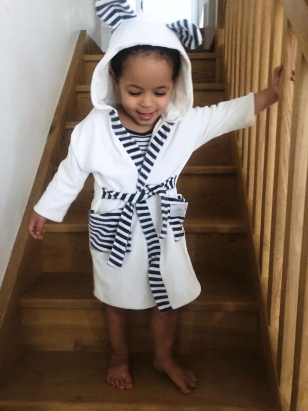 Walking down the stairs wearing the White Stripy Velour dressing gown robe by Little Earth Baby at Nurture Collective