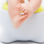 A childs feet sitting on the potty for the Nurture Collective blog on 5 tips for potty training