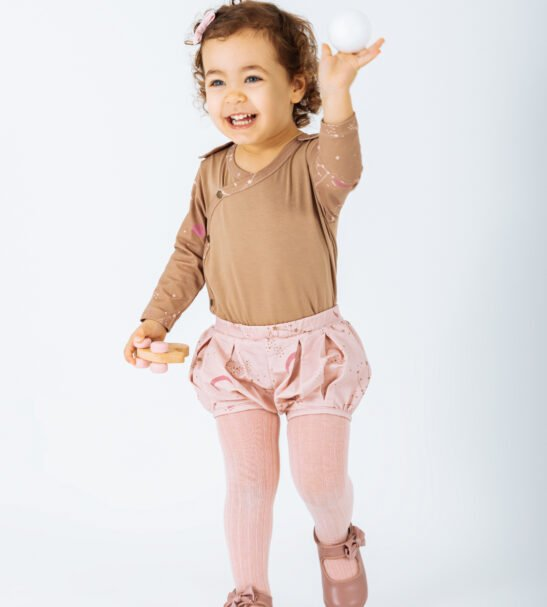 Girl wearing Body Auriga in Brown with Pink Gemini shorts by Peter Jo at Nurture Collective