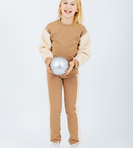 Girl Wearing the Pullover Carina Sweater in Brown and Pants Horologium in Brown by Peter Jo at Nurture Collective