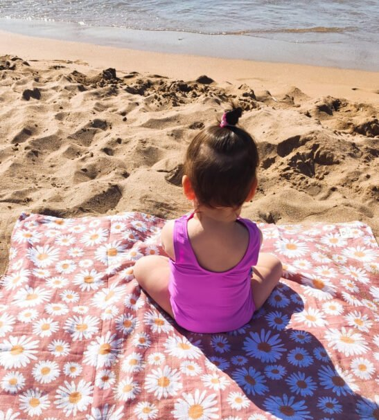 Little girl sitting one Dear Little One baby blanket Muslin in daisy print at Nurture Collective